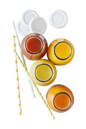 Four glass jars filled with yellow orange and red juice next to striped straws and white jar lids on white