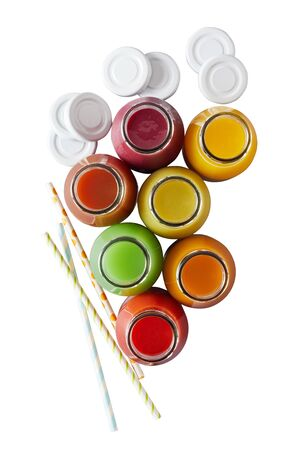 Top down view on multiple jars of nutritious fruit juice and colorful straws over plain white