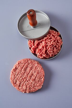 Fresh ground or minced raw beef being compressed in a patty maker while preparing homemade hamburgers with a finished circular patty alongside