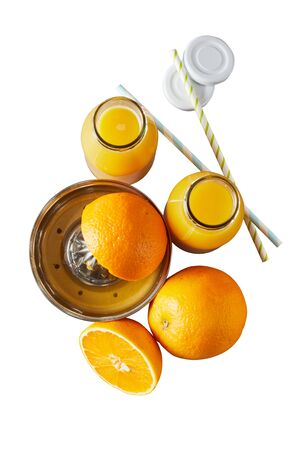 Fresh oranges being squeezed for juice on a manual squeezer with two full glass bottles alongside isolated on white in a top down view Фото со стока