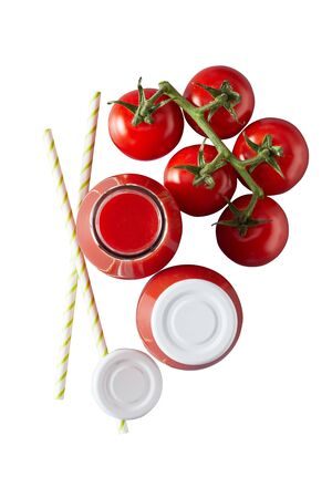 Two glass jars with white lids full of red tomato juice next to cherry tomatoes on vine and two straws