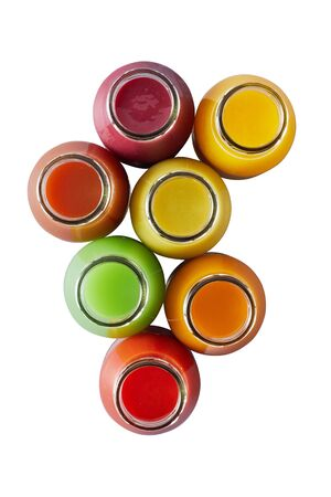 Overhead view on seven individual glass jars containing multicolored smoothies over white
