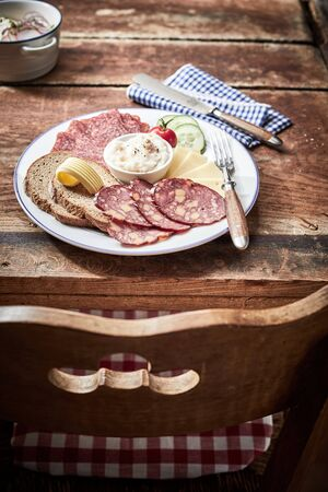 Tasty lunch platter with cheese and dried and cured wild venison sausage, rye bread and a creamy dip or spread on an old rustic table