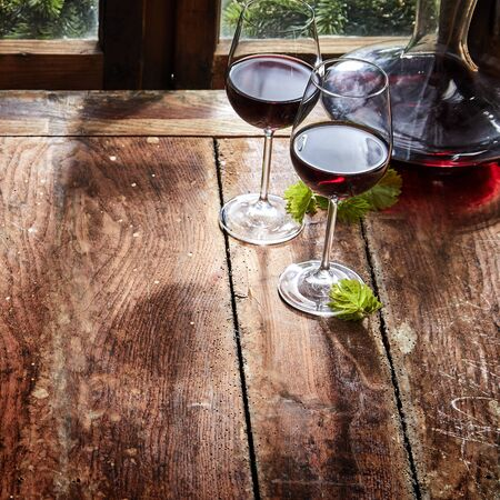 Two glasses of red wine with a decanter or carafe on a rustic wooden table alongside a window in a square high angle close up with copy space