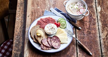 Tavern lunch with sliced wild venison sausage, salami and cheese served with rye bread and a salad on an old rustic table in a high angle view for a menu