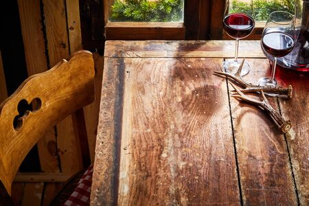 Old bare rustic wooden chair and table with deer antlers and two glasses of red wine in front of the window for food or product placement Фото со стока