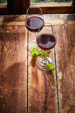 Two glasses of red wine with fresh young green vine leaves on an old rustic wooden table in front of a window in a high angle view with copy space