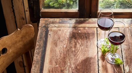 Two glasses of red wine on a rustic wooden table with fresh green leaves in front of a window and copy space for food placement in a high angle view