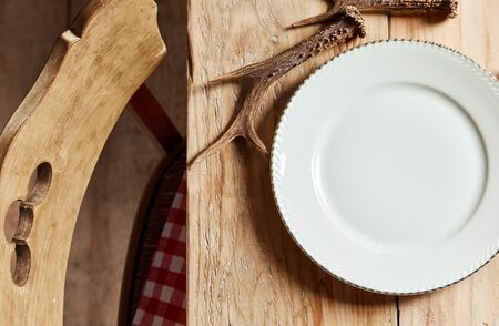 Empty white plate set beside a deer antler on a rustic wooden table ready for food to be served in an overhead view