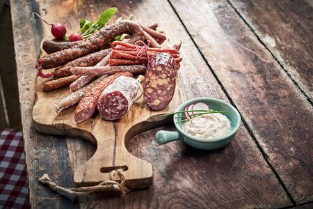 Buffet selection of dried spicy wild venison sausages on an old wooden board on a rustic table with a side dip or dressing and copy space