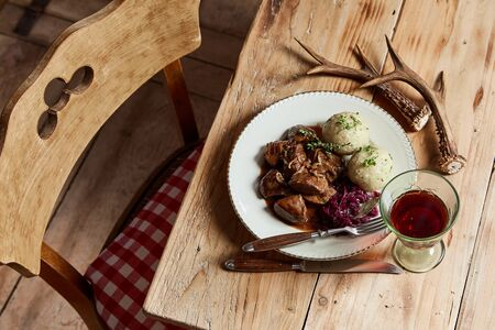 Gourmet wild venison goulash with dumplings seasoned with fresh herbs and served with red cabbage and glass of wine on a rustic table decorated with deer antlers in a high angle view Фото со стока