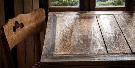 Empty old wooden table and cottage style chair in front of a window ready for product or food placement