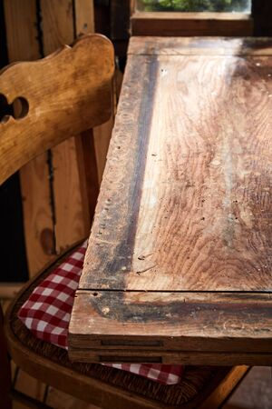 Old rustic bare empty table and chair in front of a window in a tavern or pub with copy space for product or food placement in vertical format