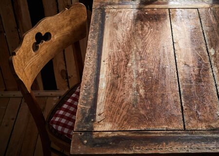 Bare rustic or vintage old wooden table and chair lit by daylight from a window for product or food placement
