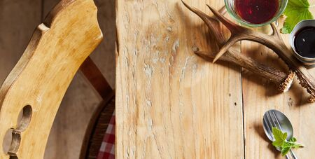 Deer antlers on a rustic wooden table with chair set with glasses of red wine and coffee with copy space for food or product placement in a panorama banner