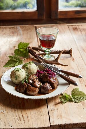 Plate of venison goulash with dumplings and fresh herbs on a rustic tavern table with a glass of red wine lit by daylight from a window