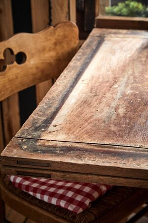 Empty old wooden table with vintage chair in a close up low angle view for food or product placement Фото со стока
