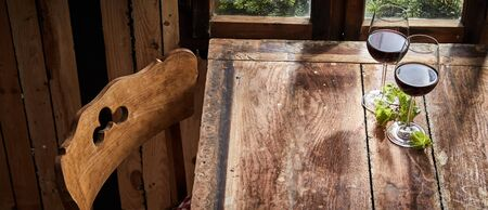 Panorama banner of red wine on a rustic bar table with fresh green vine leaves and old cottage style chair in daylight from a window with copy space on the table top
