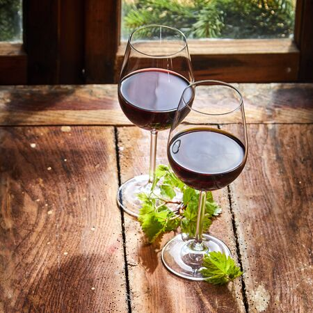 Two glasses of red wine with green vine leaves alongside a window on a rustic wooden worm ridden table in square format