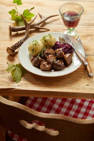 Plate of rich spicy wild venison goulash served with red cabbage and dumplings garnished with herbs on a rustic wooden table with red wine and deer antlers viewed over a chair Фото со стока