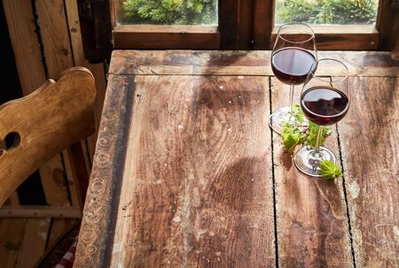 Two glasses of red wine with fresh green leaves standing on an old rustic table in front of a window with copy space in a high angle view