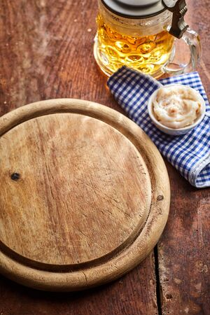Empty old round wooden board with tankard of beer, napkin and bowl of dip on an old wooden able viewed from above for food placement