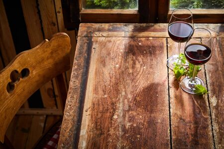 Two glasses of red wine served on a rustic old table with copy space for product or food placement in light from a window