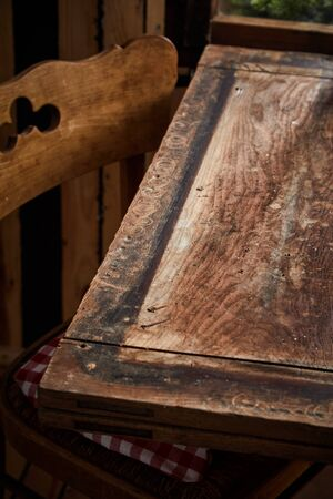 Partial view of a bare old rustic wood table and chair with copy space for placement of food or products in a vertical view Фото со стока