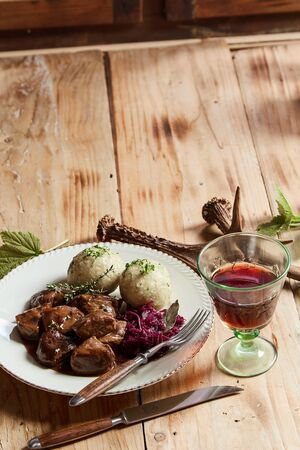Gourmet wild venison goulash with dumplings and shredded red cabbage served with a glass of red wine on a table with decoration of antlers and copy space