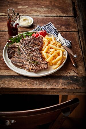Barbecued or grilled T-bone steak and French fries served with salad trimming on an old rustic table in a tavern for lunch