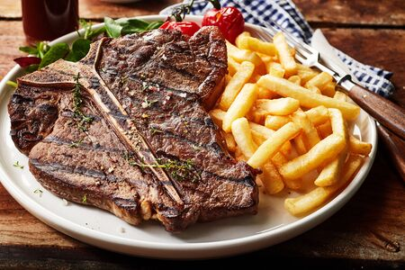Tasty grilled T-bone steak seasoned with herbs and spices served with deep fried potato chips and salad in a close up view for menu advertising