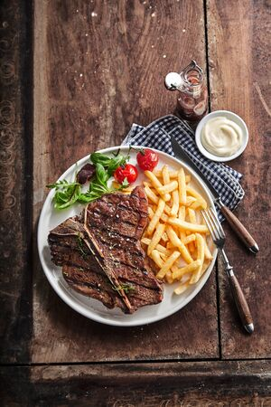 Grilled lean T-bone steak with golden potato chips and salad served with a dip or dressing on a rustic wooden table in a top down view with copy space