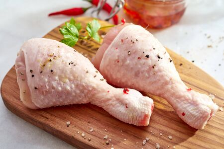 Two raw chicken drumsticks with their skin sprinkled with chili flakes and spices displayed on a wooden chopping board in a close up view