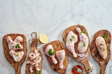 Bottom border on marble with raw chicken portions displayed on wooden chopping boards sprinkled with fresh herbs and spices and basted with marinade ready for cooking