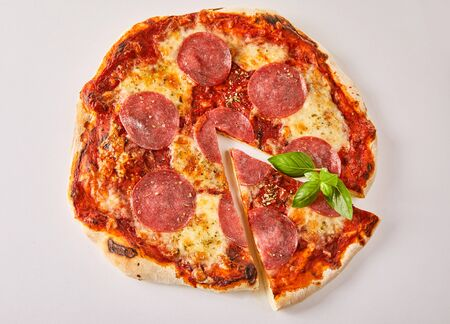 Overhead view of a traditional salami Italian pizza with a single cut slice isolated on white for menu advertising
