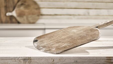 Old vintage empty wooden pizza paddle on a rustic white table with copy space for food or product placement