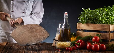 Chef holding a wooden paddle in a pizzeria above a rustic table with assorted fresh ingredients for Italian cuisine in a panorama banner