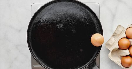 An egg on a hot pan, top down view Stock Photo