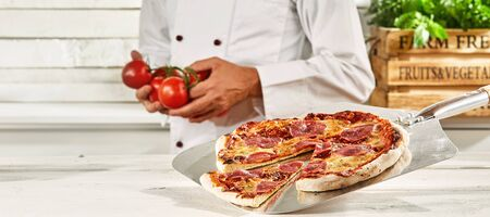 Fresh oven-fired salami pizza with melted mozzarella cheese and spicy sausage and a uniformed chef holding tomatoes standing behind in a white rustic kitchen in a panorama banner