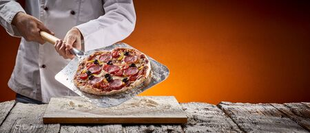 Chef with a delicious homemade pepperoni pizza displaying it on a metal paddle after removing it from the oven in a pizzeria in a rustic panorama banner with copy space with glow of the fire