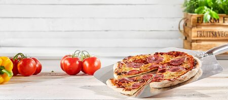 Panorama banner with a tasty pepperoni or spicy salami pizza with a wedge cut served on a metal pizzeria paddle with fresh ingredients and copy space
