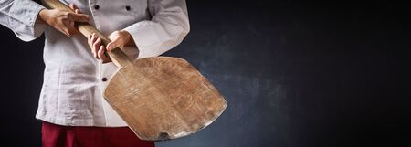 Chef holding an empty wooden pizza paddle in a close up on his hands in a panorama with dark background and copy space for food or product placement