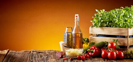 Ingredients for Italian cuisine in a pizzeria with parmesan cheese, olive oil, tomatoes, basil and sweet peppers on a rustic table over a brown background with copy space in a wide angle panorama with glow of the oven fire