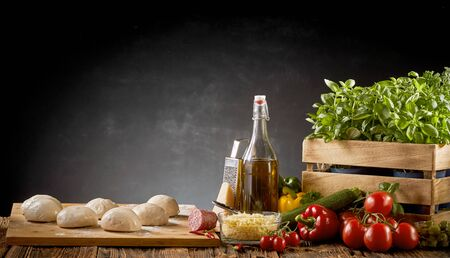 Fresh organic ingredients for an Italian pizza with individual portions of uncooked dough, basil, tomatoes, cheese, sweet peppers and olive oil over a dark background with copy space