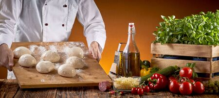 Chef preparing fresh raw dough for pizzas in a pizzeria carrying a board with individual portions to a table with fresh topping ingredients in a panorama banner
