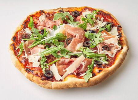 Tasty prosciutto, rocket and olive Italian pizza with parmesan cheese and tomato on a crispy oven-fired base over white