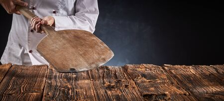 Chef holding an empty wooden pizza paddle over an old rustic kitchen table in a panorama banner with copy space for product or food placement
