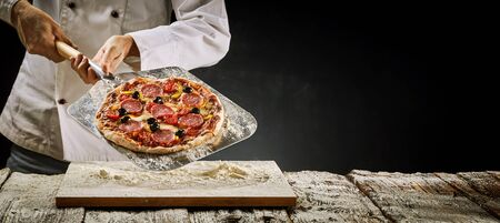 Chef removing an Italian salami pizza from the oven displaying it on a metal paddle over a floured wooden board in a rustic panorama banner with copy space