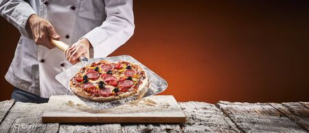 Chef in a pizzeria with homemade salami pizza displayed on a metal paddle over a floured board in front of the glow of the fire in the oven in a rustic panorama banner with copy space