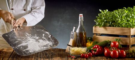 Chef holding a metal paddle with flour ready for making a traditional Italian pizza with ingredients on a rustic table in a panorama banner Imagens